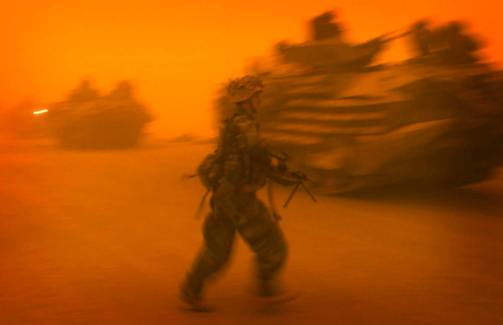 A soldier hurries back to his amphibous assault vehicle during a dust storm that paralyzed the U.S. military's surge north.