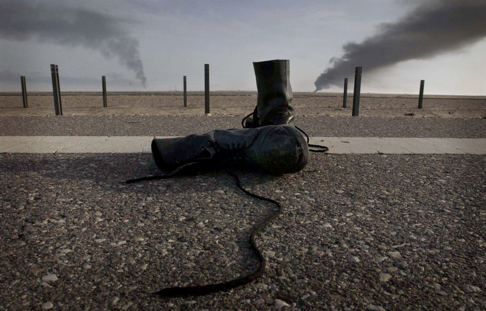 A pair of boots sit on the edge of the highway, abandoned by a deserting Iraqi soldier.
