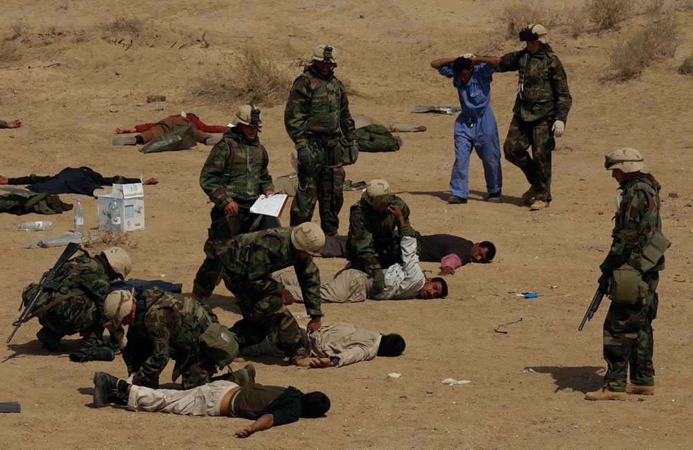 American soldiers process Iraqi military POWs.
