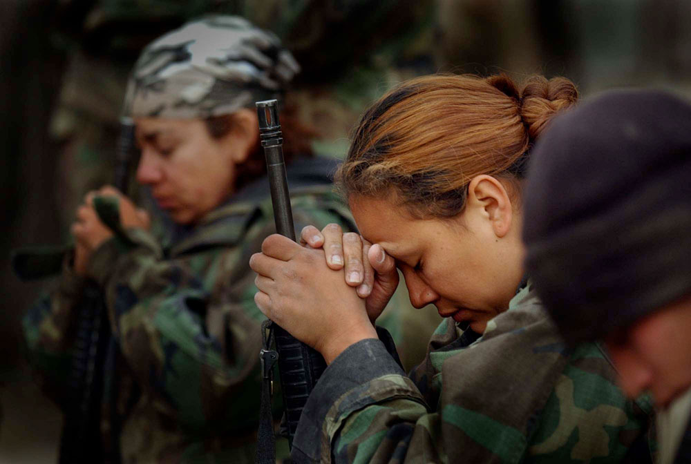 U.S. Marines pray during a Sunday Mass at a field chapel on the way north to Baghdad during the initial invasion into Iraq in 2003. While many in the military are devoted to their faith, the chaplain says the numbers going to services soars when in a combat zone.