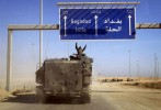 A U.S. Marine raises his arms in triumph as he passes under the first sign for Baghdad on the road north from Kuwait.