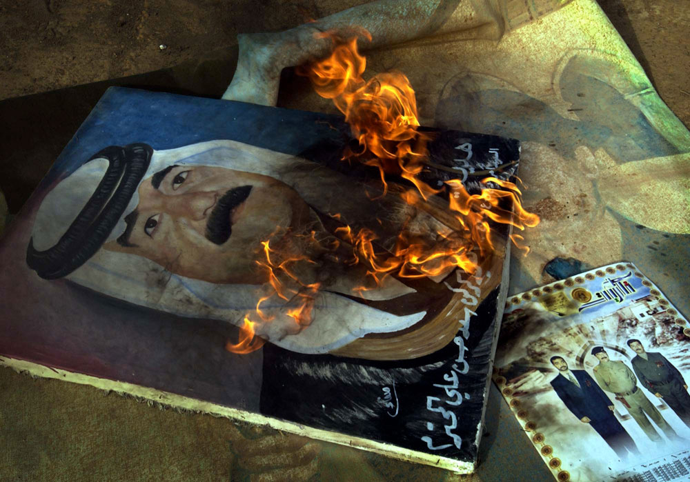 A painting of Saddam Hussein is set alight after being pulled from a military post on the outskirts of Baghdad.