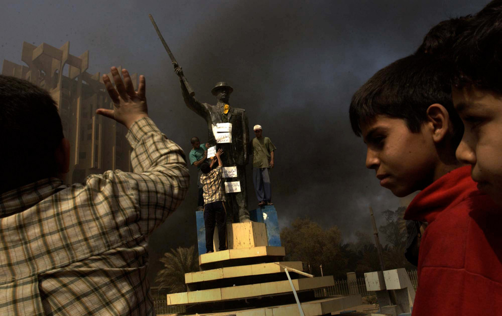 Boys watch as attempts are made to pull down a statue of Saddam Hussein as looted burnings burn. Looting was widespread throughout Iraq after the collapse of the regime.