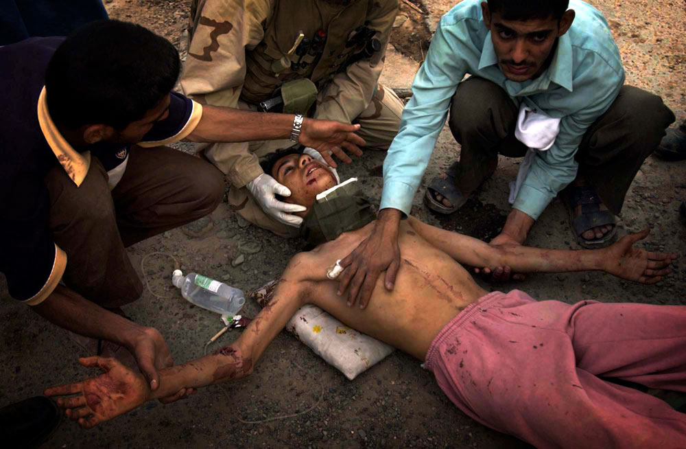 A boy lies wounded on the ground after being shot by a shopowner for attempting the loot the business. The wounds were treated and the boy transported to a U.S. military hospital.