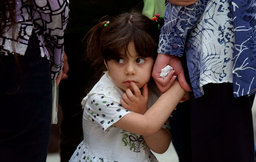 A girl glances back as she lives a Christian Good Friday service in Baghdad. With the weight of Saddam Hussein's regime lifted, the Christian minority is concerned about the future in the predominantly Muslim country.