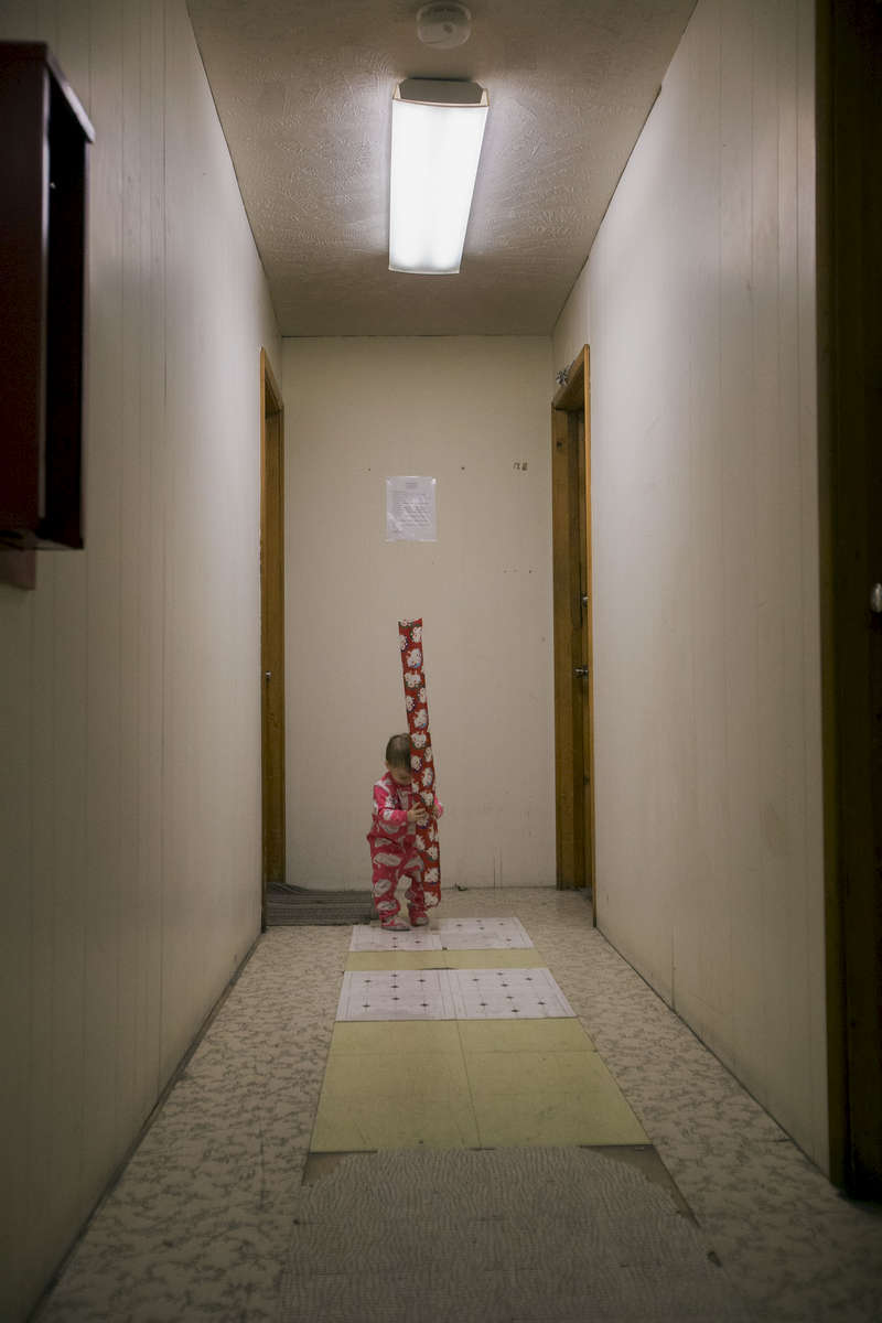 1-year-old Harley Savard holds Christmas wrapping paper in the hallway near the apartment she lives in with her parents, Caitlin Savard and Robbie Savard, above Jim's Landing in Springfield on Friday, November 21, 2014. The fire marshal's office notified tenants in the Jim's Landing building in Springfield on Friday, November 21, 2014 that they need to vacate within 48 hours. Fire officials found numerous code violations after a fire on November 11, 2014 that they say makes the building inhabitable. (Andy Nelson/The Register-Guard)