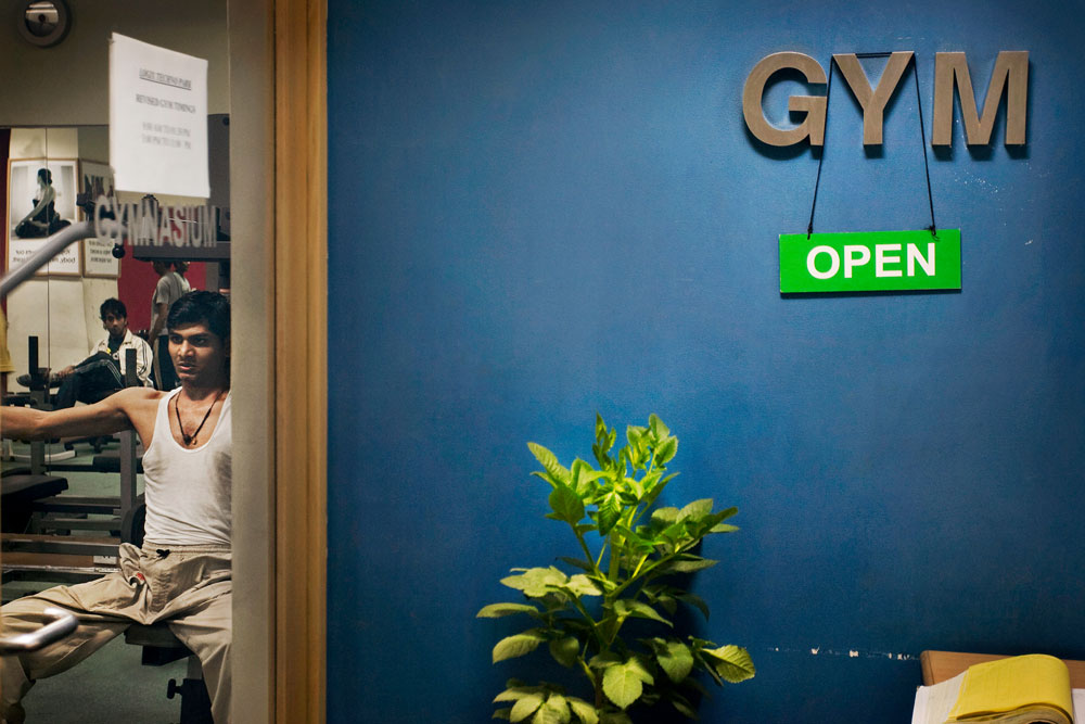 India, Mumbai, February 2008.A young man exercising inside an office space. The western life-style has entered into the Indian mentality. New office spaces and buildings are being built all over Mumbai.