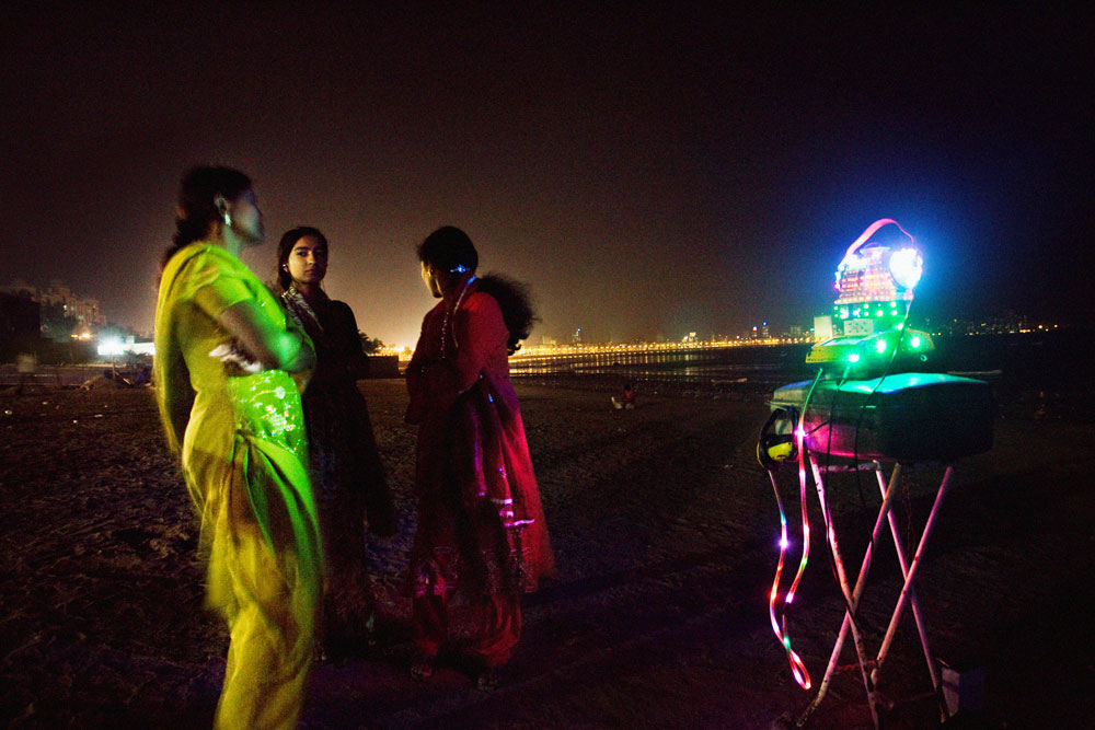 Chopati beach, Mumbai, India, February 2008Three girls standing in front of a crazy hand made with fluorescent colors fortune teller at Chopati Beach in Mumbai.