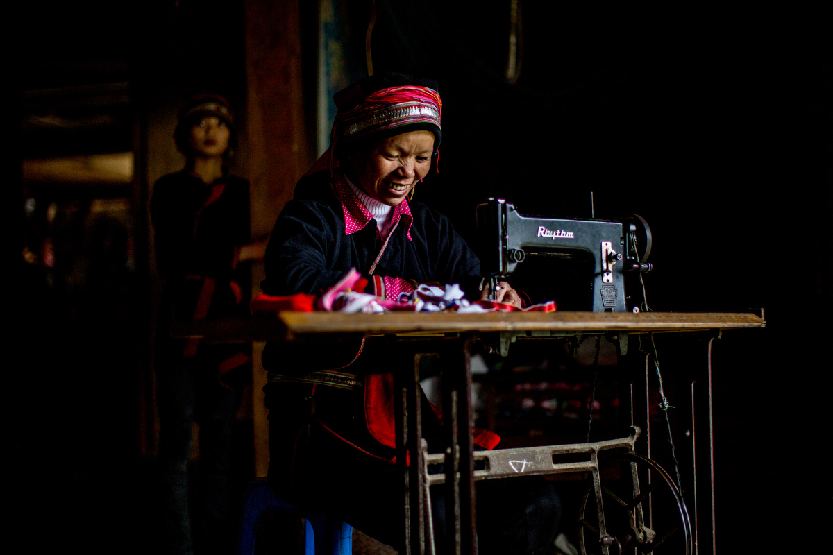 Seamstress Tan Thi Song works at her home located along Highway 176A in Ha Giang Province on January 9th, 2015.Highway 176A is one of the most dangerous and most difficult roads to reconstruct because of its location embedded into the treacherous mountains of Ha Giang. ADB project to upgrade this highway makes it more economical for people like Thi to have her goods reach markets in neighboring towns.
