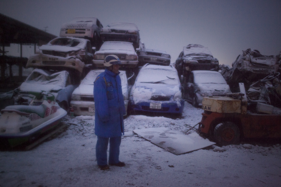 Akira Sugawara, 56, walks through a massive car pile where he works as a security guard. Vehicles destroyed or left behind in the chaos of last years tsunami are piled high, waiting for their owners to come and claim them in Ishinomaki, Japan.