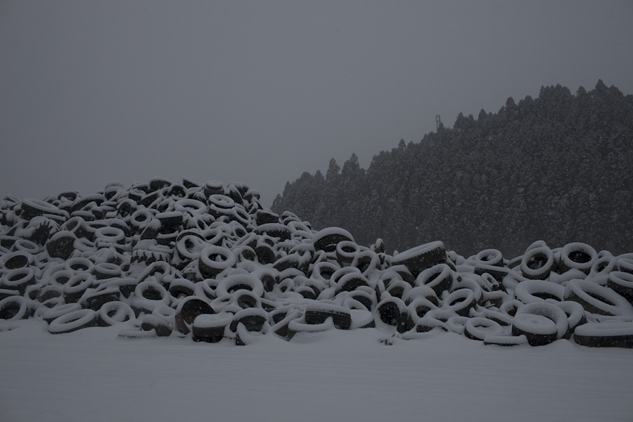 Tires lie beneath a blanket of freshly fallen snow in Minamisanriku, Japan.