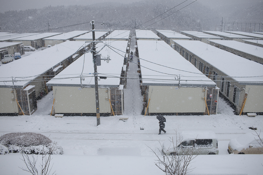 Residents walk in front of a temporary housing site near Minimisanriku, Japan. Hundreds of thousands of Japanese are still displaced one year after an earthquake and tsunami devastated the Tohoku coastline.