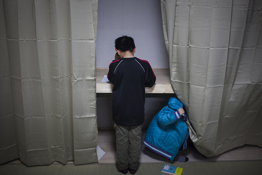 Two young boys finish their homework at a community center in a temporary housing complex near Minamisanrku, Japan.