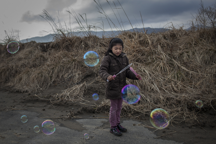 Eight year old Hikari Oyama blows bubbles with her Grandmother after visiting a memorial at Okawa Elementary School. Seventy seven children were killed when a tsunami struck the school on March 11, 2011 near Ishinomaki, Japan. {quote}I thought bubble suits better for children rather than incense sticks [for a memorial]...and it always makes people laugh and relax,{quote} Oyama's grandmother said.