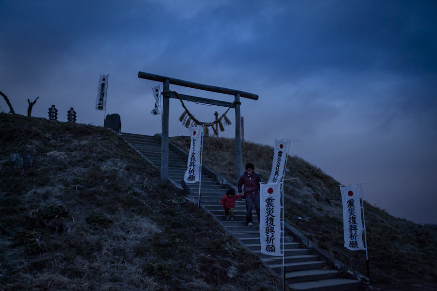A father leads her daughter down the steps of a memorial site at Hiyoriyama in Natori, Japan, a small hill used by locals attempting to flee the 2011 earthquake and tsunami.