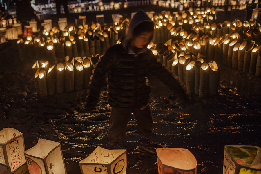 A boy runs between paper lanterns lit to commemorate the one year anniversary of an earthquake and subsequent tsunami that left more than 19,000 people dead or missing. March 12, 2011, Natori, Japan.