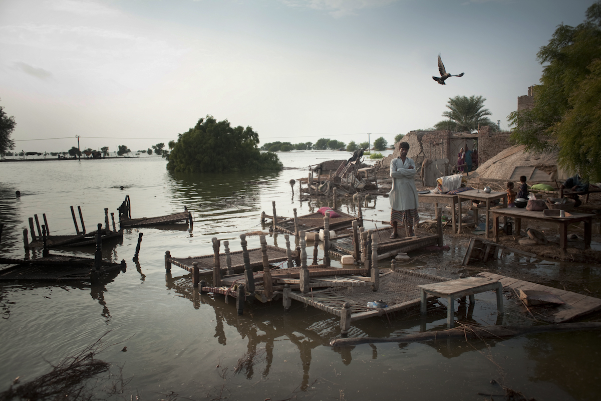 A flood victim stands with his belongings, waiting to be evacuated from his flood destroyed village on September 11, 2010 near the village of Kalimuri, in Sindh province, Pakistan.