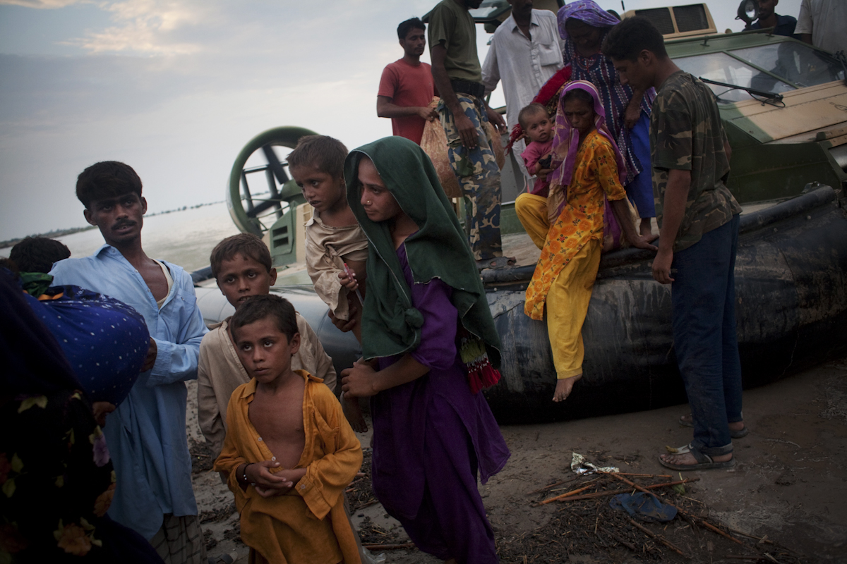 Women deboard a Pakistani Navy hover craft after being rescued from their village. They were then taken to an Army refugee camp, with no idea how long they would have to stay.