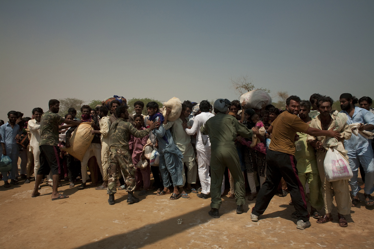 Villagers fight to get on a rescue helicopter in Faridibad, Sindh province. They had been trapped for days, surrounded by at least 20 kilometers of water, without access to food or clean water.