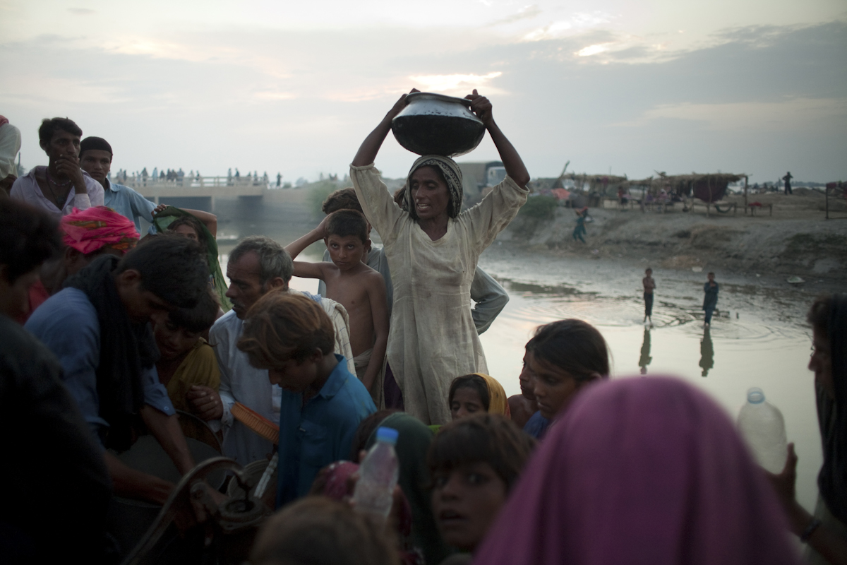A woman collects water from a pump at a makeshift IDP camp in Kalimuri, Sindh Province, Pakistan, on September 12th, 2010.