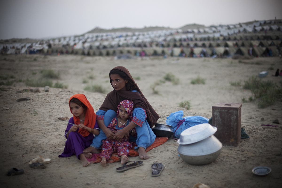 Sakina, 22, sits with her daughters Satara and Kahalda and their few belongings at a Pakistan Army run IDP camp in Sehwan Sharif, Sindh Province, Pakistan, waiting to be registered in order to receive a tent. Her husband is a labourer; on the day her village flooded, he went to work and the waters rose while he was gone. Sakina and her daughters were evacuated that day, and she has not seen her husband since.