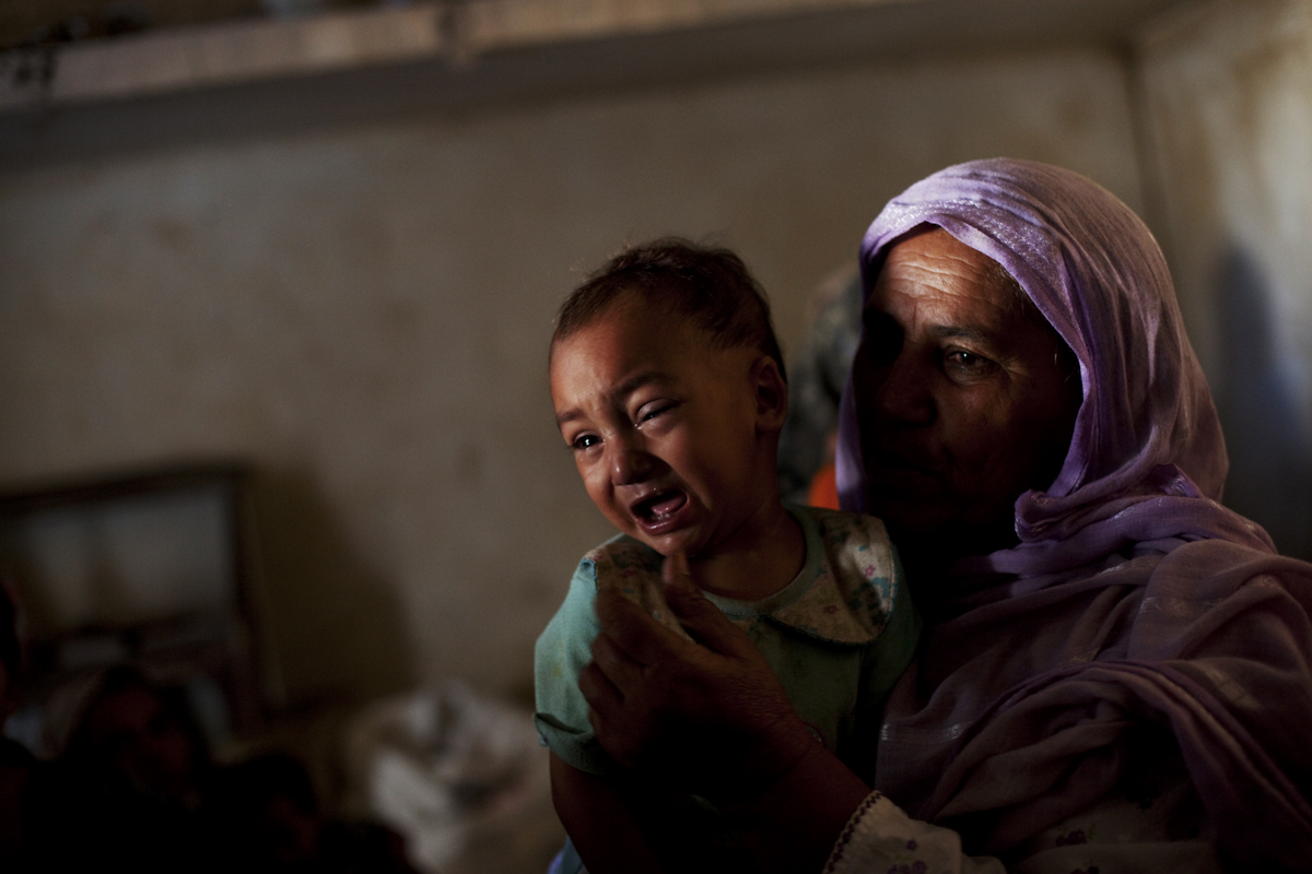 A young boy with an eye infection brought on my unsanitary conditions from the floods cries in his grandmother's lap on September 20th in Nowshera, Pakistan