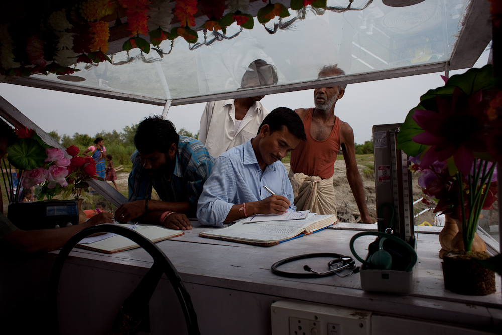 Since 2005, travelling boat clinics have brought the first consistant health care to the river islands. Here, community health workers check in patients through the front window of one of the boats. A partnership between the Center for North Eastern Studies (a local research group), the Assamese government, and UNICEF has provided expanding care over the last four years.