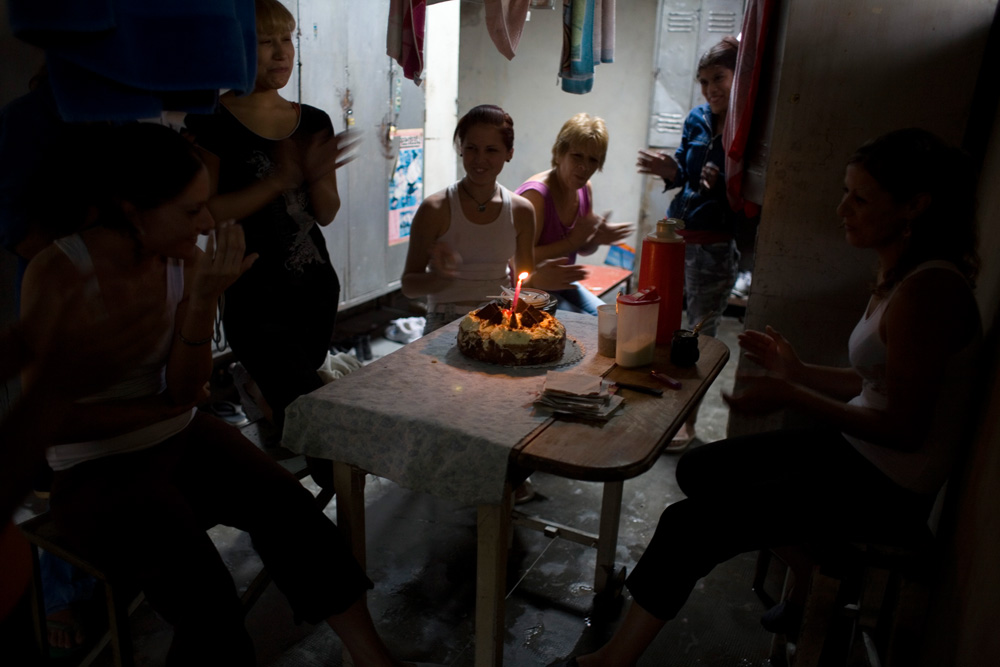 Women celebrate a birthday inside the factory dressing room. Despite social rifts due to differences of opinion on how to spend factory money, workers sitll interact on a very personal level, celebrating birthdays and spending weekends together.