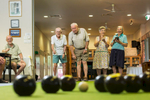 Retirement village residents enjoying a game of indoor lawn bowls