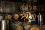 Mature couple doing a wine tasting amongst wine barrels aat Cofield Wines in Wahgunyah, Victoria