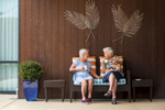 Two female aged care residents sitting next to each other, enjoying a chat over tea