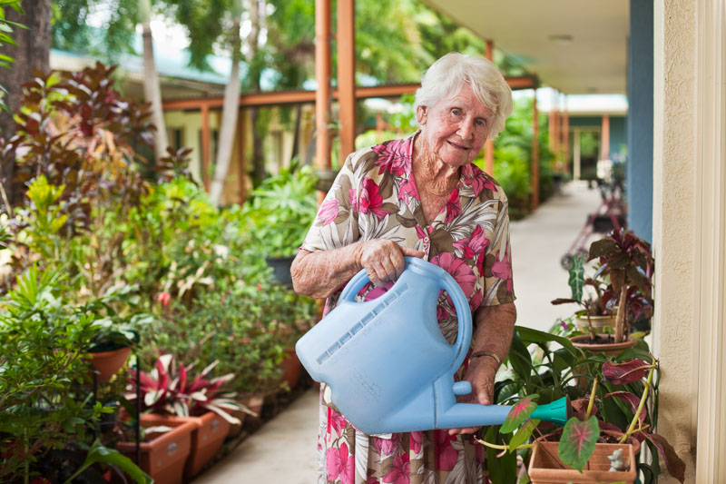 Portrait of an assisted living community resident watering her garden plants