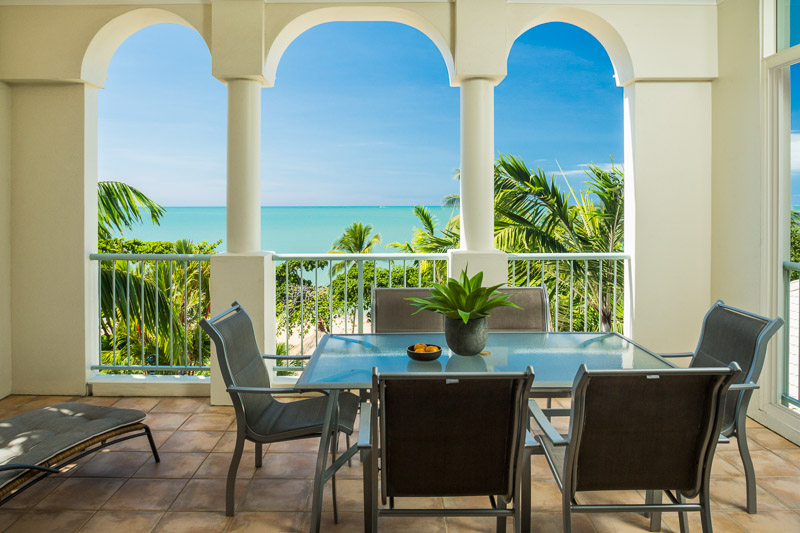 Apartment terrace overlooking tropical beach at Sea Change Beachfront Apartments
