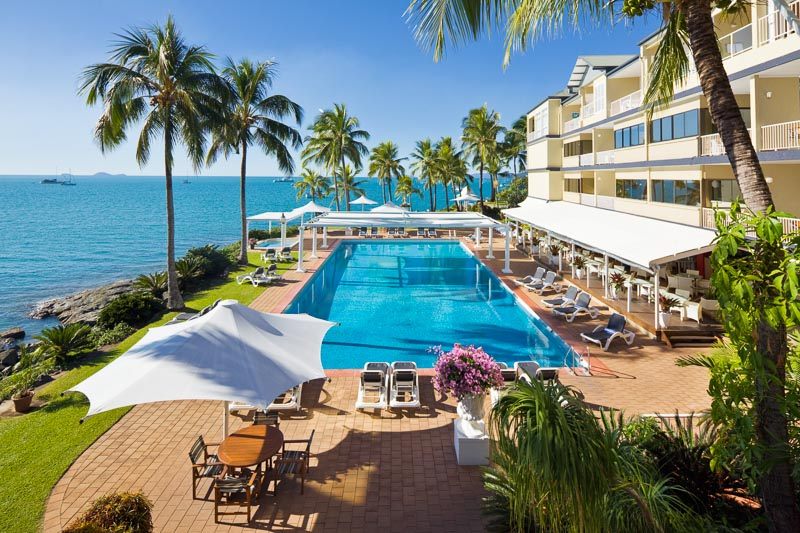 Waterfront resort pool surrounded by palm trees at the Coral Sea Resort, Airlie Beach