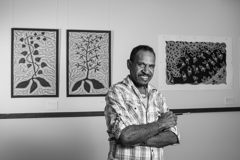Portrait of indigenous artist standing in front of gallery artwork, Cairns