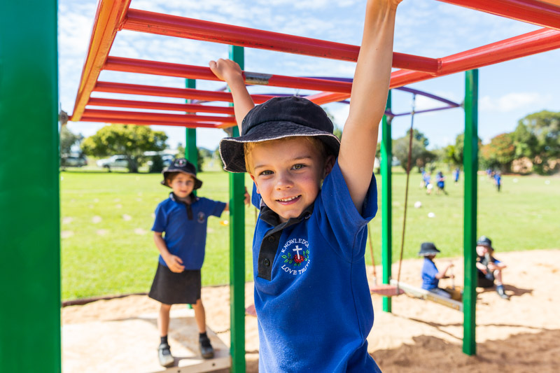 Portrait of a young school child at play on the monkey bars in the playground