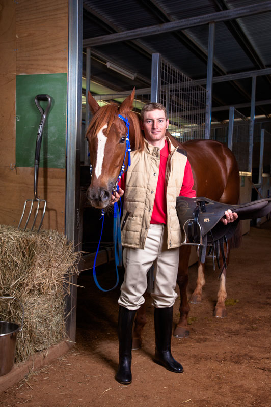Portrait of jockey standing beside horse in stables