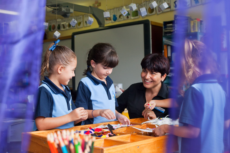 A smiling teacher and young students during art class