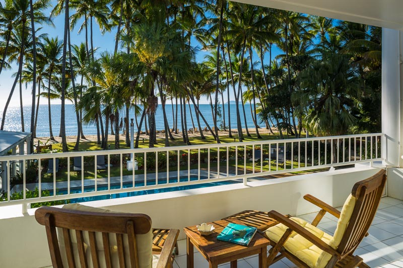 View from hotel room balcony overlooking pool and tropical beach at Alamanda Resort Palm Cove