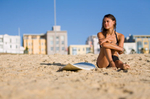 Young female surfer sitting on beach sands next to her board
