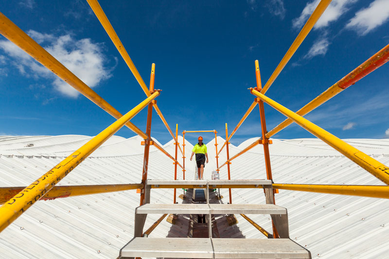 Worker walking across scaffolding on the roof of the Cairns Convention Centre