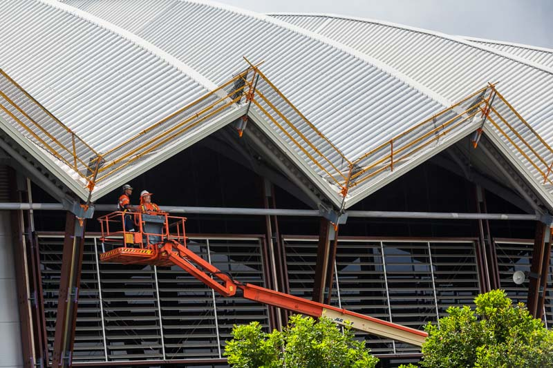Maintenance workers in cherry picker looking at roof of the Cairns Convention Centre