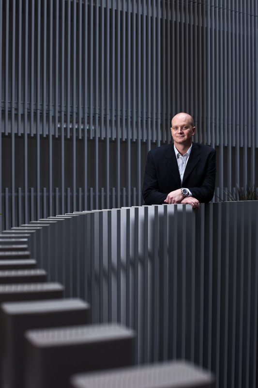 Portrait of businessman, Mark Turnbull standing in atrium of hotel, Cairns