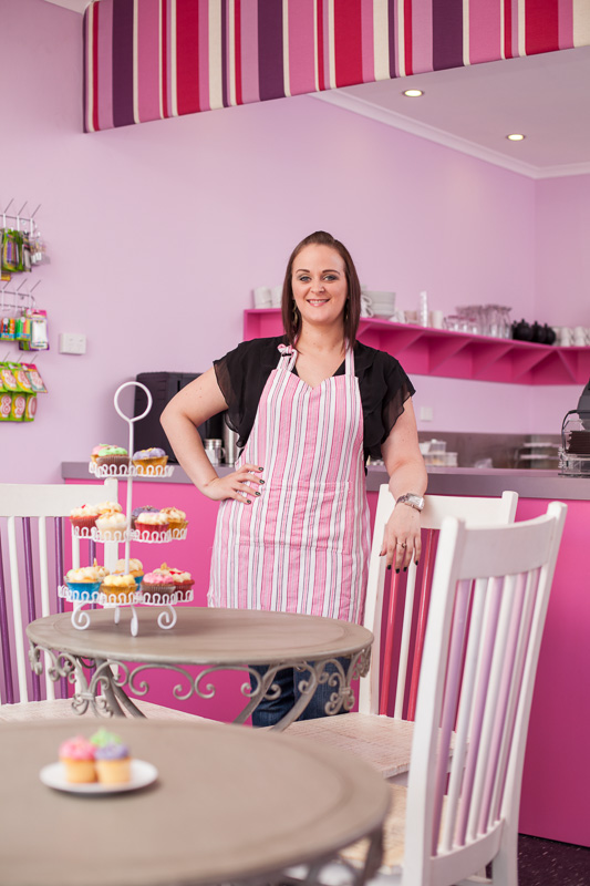 Portrait of female business owner in her cupcake bakery and cafe, Cairns