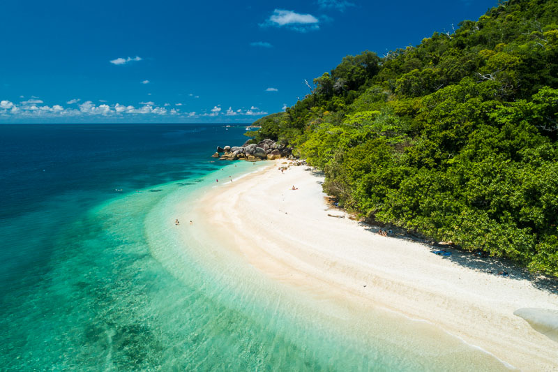 Aerial view of clear waters and white sands of Nudey Beach on Fitzroy Island, Cairns