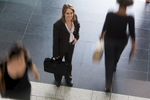 Portrait of businesswoman with scene of blurred people walking by