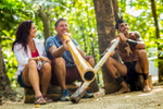 A tourist couple getting a didgeridoo lesson by indigenous performer at Tjapukai Aboriginal Cultural Park, Cairns