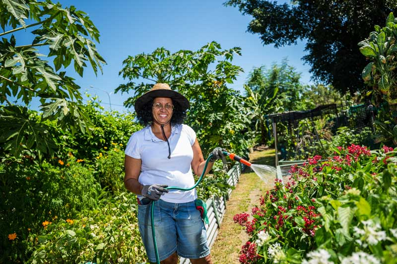 Portrait of a woman watering plants at a community garden