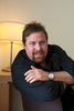 Portrait of actor Shane Jacobson sitting on chair, Cairns