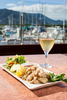 Dish of salt and pepper squid with glass of wine overlooking the marina in Cairns